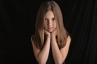 Girl (10-12) on black background portrait