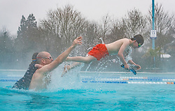 © Licensed to London News Pictures. 02/03/2018. London, UK. Doug O'Gorman plays with his children Lola and Alfie (R)   as they brave the cold and snow at Hampton heated outdoor pool in south west London. The 'Beast from the East' and Storm Emma have brought extreme cold, ice and heavy snow to the UK. Photo credit: Peter Macdiarmid/LNP