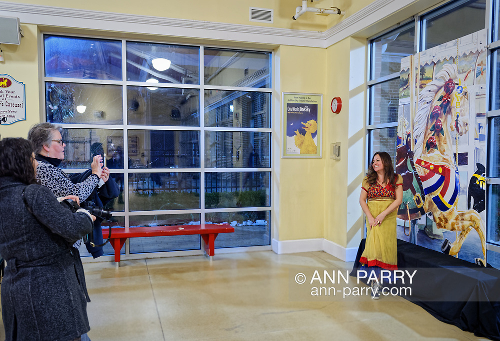 Garden City, New York, USA. March 9, 2019.  L-R, JEAN SMYTH-CROCETTO watches as MAUREEN LENNON captures cell phone photos of RITA CAVANAGH, Baldwin Civic organization Beautification Committee, Chair posing next to mural of closeup of Nunley's Carousel lead horse. Event was held at historic Nunley's Carousel in its Pavilion on Museum Row on Long Island.