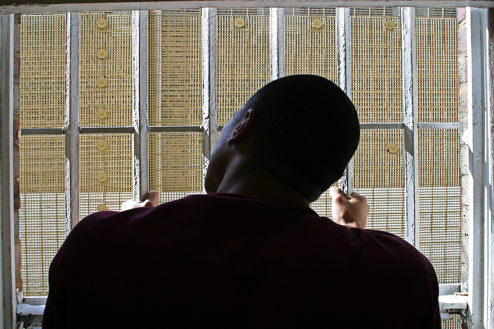 A prisoner looks out between the bars on his cell window. HMP Wandsworth, London, United Kingdom