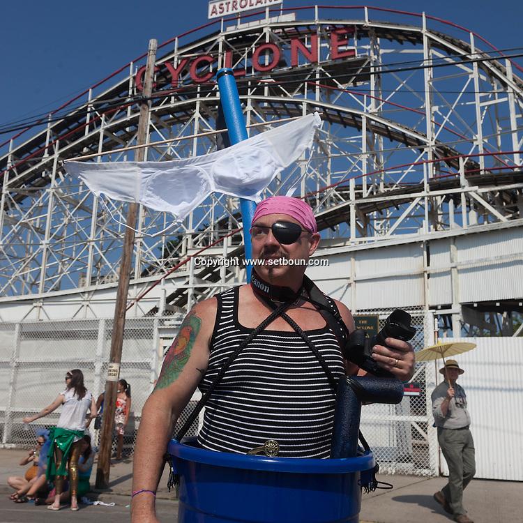 New York. Brooklyn. Coney island crowd  in front of the roller coaster on  the boardwalk in Coney island beach  in summer . people swimming  United States  / la foule devant le grand huit de Coney island en ete.  Brooklyn  New York - Etats Unis