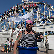 New York. Brooklyn. Coney island crowd  in front of the roller coaster on  the boardwalk in Coney island beach  in summer . people swimming  United States  / la foule devant le grand huit de Coney island en ete.  Brooklyn  New York - Etats Unis
