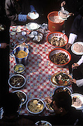 During a celebration of the first electricity to come to this village in Bhutan, visiting dignitaries join village elder Namgay at a buffet of red rice, potatoes, tomatoes, cucumbers, beef, chicken, and a spicy cheese and chili pepper soup (close-up of table shown here). The villagers have been stockpiling food for the event. (Supporting image from the project Hungry Planet: What the World Eats.) The Namgay family living in the remote mountain village of Shingkhey, Bhutan, is one of the thirty families featured, with a weeks' worth of food, in the book Hungry Planet: What the World Eats.