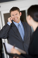 Business man using mobile phone with colleague in office