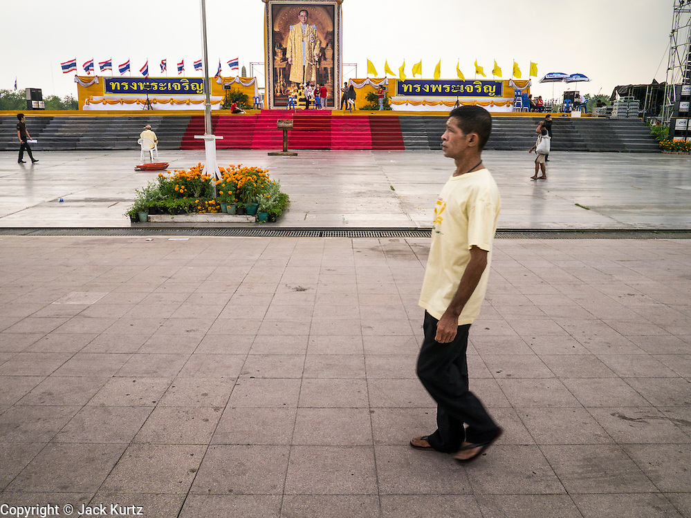 04 DECEMBER 2012 - BANGKOK, THAILAND:  A man wearing a yellow tee shirt walk across Sanam Luang and past a portrait of Bhumibol Adulyadej, the King of Thailand. The King, whose official color is yellow, celebrates his 85th birthday Wednesday, Dec. 5. People frequently wear yellow to show their support for the monarchy. He is expected to make a rare public appearance and address the nation from Mukkhadej balcony of the Ananta Samakhom Throne Hall in the Royal Plaza. The last time he did so was in 2006. His birthday is a public holiday in Thailand and hundreds of thousands of people are expected to jam the streets around the Royal Plaza and Grand Palace to participate in the festivities.   PHOTO BY JACK KURTZ