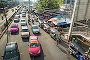 "26 SEPTEMBER 2012 - BANGKOK, THAILAND: Traffic on Rama IV Road in front of Khlong Toey Market in Bangkok. Khlong Toey (also called Khlong Toei) Market is one of the largest ""wet markets"" in Thailand. The market is located in the midst of one of Bangkok's largest slum areas and close to the city's original deep water port. Thousands of people live in the neighboring slum area. Thousands more shop in the sprawling market for fresh fruits and vegetables as well meat, fish and poultry.     PHOTO BY JACK KURTZ"