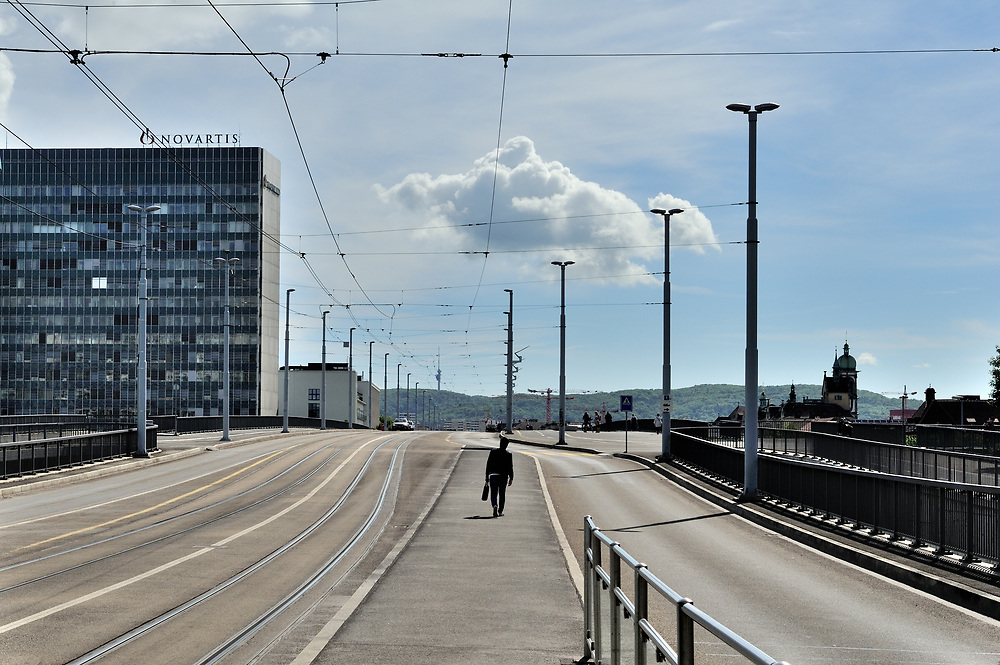 A man walks over a Rhine bridgeafter leaving Novatis Campus,  the headquarters of this phramaceutical giant,  a gated village within the city, including buildings by star architects.<br /> <br /> Basel, straddling the Rhine, and bordering both Germany and France, is a global centre for the pharmaceutical  industry &ndash; &lsquo;big pharma&rsquo;, with hundreds of biotech and &lsquo;life sciences&rsquo; companies ranging from start-ups to two of the top five global companies: Novatis and Hoffmann La Roche.<br /> <br /> The industry provides roughly 40% of total Swiss exports. The chemical and pharmaceutical industry currently employs around 65,000 people in Switzerland and over 355,000 internationally.