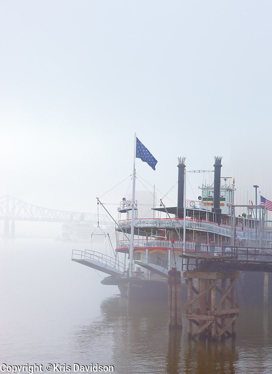 The Steamboat Natchez docked by the French Quarter on the Mississippi on a foggy morning.