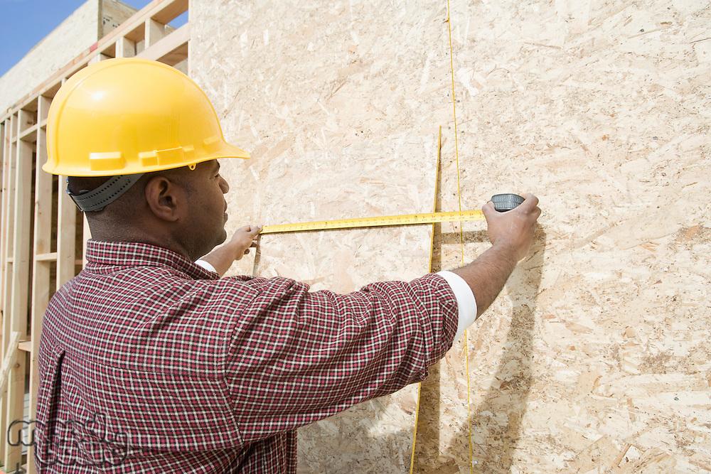 Construction worker measuring building