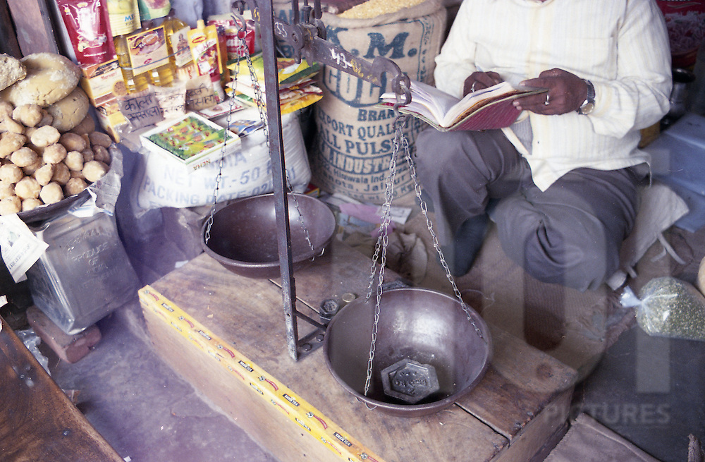 A spice vendor calculates a customers bill, Jaipur, India, Asia.