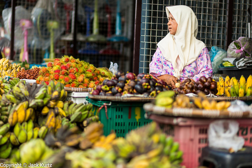 09 JULY 2013 - PATTANI, PATTANI, THAILAND: A Muslim fruit vendor in the market in Pattani.  Pattani, along with Narathiwat and Yala, are the only three Muslim majority provinces in Thailand.     PHOTO BY JACK KURTZ