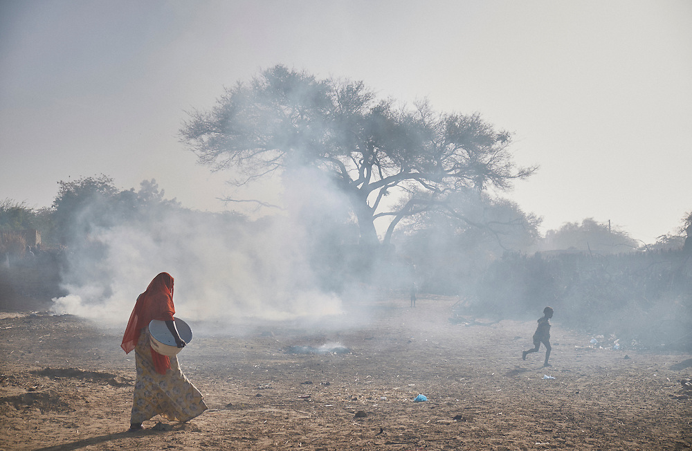 A women walks through burning rubbish in the village of Boudoum near the border with Nigeria on the outskirts of Diffa, Niger on February 13, 2016. Displaced people from Niger and Nigeria are sheltering in the village after fleeing frequent attacks at the nearby border, less than a kilometre away. An attack by Boko Haram on the Nigerien army had taken place two days before.