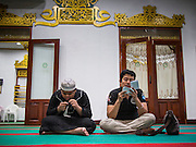 26 JULY 2013 - BANGKOK, THAILAND: Men pray in Haroon Mosque in Bangkok before Iftar. Iftar is the Muslim meal that breaks the day long fast during Ramadan. Ramadan is the ninth month of the Islamic calendar, and the month in which Muslims believe the Quran was revealed. The month is spent by Muslims fasting during the daylight hours from dawn to sunset. Fasting during the month of Ramadan is one of the Five Pillars of Islam. Muslims believe that the Quran was sent down during this month, thus being prepared for gradual revelation by Jibraeel (Gabriel) to the prophet Muhammad.            PHOTO BY JACK KURTZ