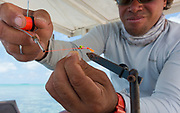 Itu Davey ties up a quick Cook Island bone pattern under the shade structure of his boat.