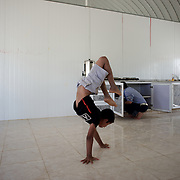 August 09, 2013 - Zarqa, Jordan: A syrian child demonstrates his handstand skills at the men's eating area of Mrigb Al-Fuhud refugee camp, also known as Emirates-Jordanian camp, 20 kilometres east of the Jordanian city of Zarqa.<br /> The 10 million USD camp, which has 750 caravans, a hospital, and a school and can take up to four thousand people, first opened in April 2013 and was paid for by the United Arab Emirates. Work is underway to house a total of 20 thousand by the end of the year. <br /> In contrast with the two other camps in the area, Mrigb Al-Fuhud as been classified by many as a 'five star' camp due to impressive housing facilities provided to the refugees. (Paulo Nunes dos Santos/Al Jazeera)