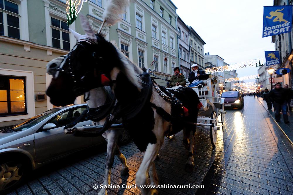 Horse carriage on Grodzka street at dusk in winter, Krakow, Poland