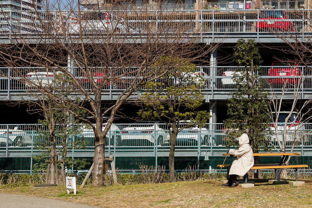 On older Japanese woman wrapped up against the cold, sits on a bench in a small park with a multi-storey carpark behind. Shinagawa, Tokyo, Japan. Friday February 9th 2018