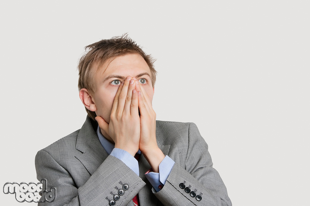 Close-up of a shocked businessman with hands covering mouth over light gray background