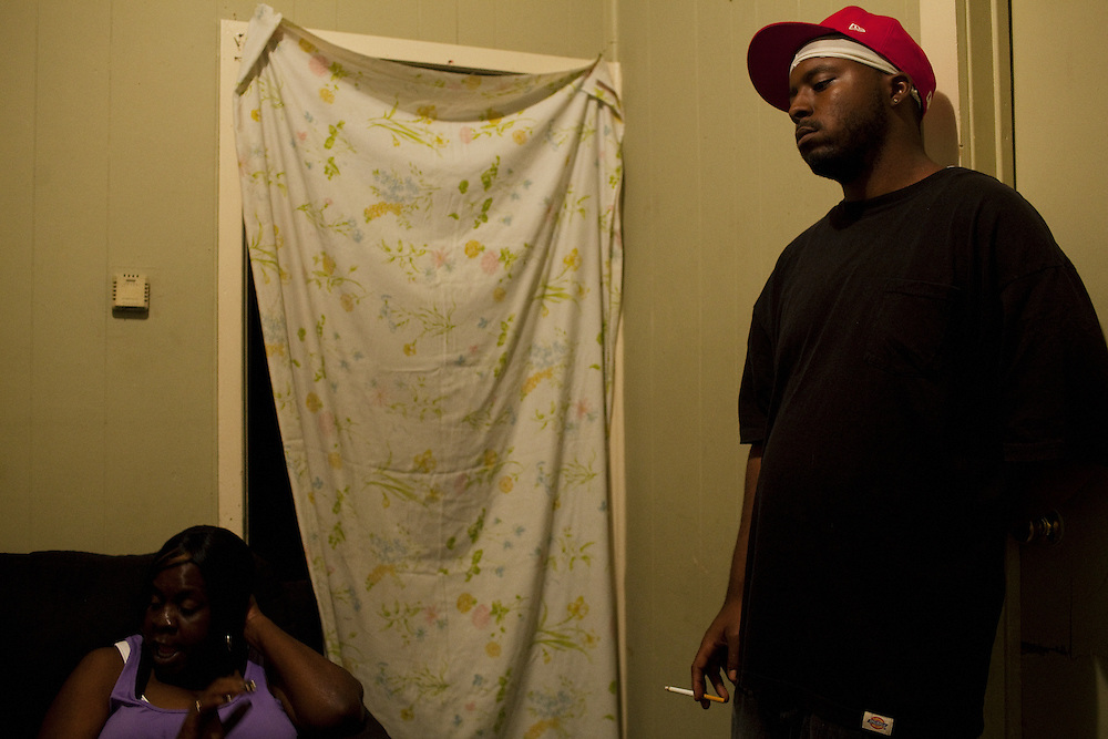 Jabari Wilson leans against the wall of his sister's home while his mother Ellen talks in the Baptist Town neighborhood of Greenwood, Mississippi on May 27, 2011.