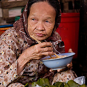 Old woman market vendor eating bowl of noodles (Hoi An, Vietnam - Nov. 2008) (Image ID: 081108-0658271a)