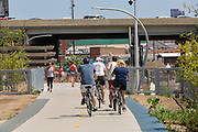 Bicyclists ride along the 606 elevated bike trail, green space and park built on the old Bloomingdale Line in the Wicker Park neighborhood in Chicago, Illinois, USA
