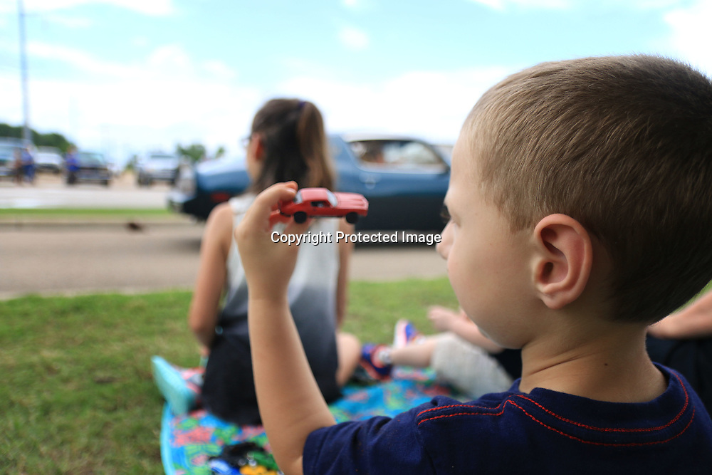 4-year-old William Parker plays with one of his toy cars while the wave of muscle cars from The Bandit Run pass by him at the Tupelo Automobile Museum Monday Afternoon.