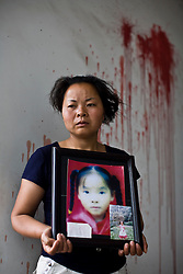 Wu Xianfang, 35, holding a picture of her daughter Wei Yu, 10, is seen at Fuxin No.2 Primary  School in Wufu, Sichuan province May 31, 2008.