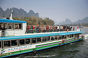 Tourist boat from Guilin Tourism Co. Ltd carries Chinese tourists along Li River between Guilin and Yangshuo, China