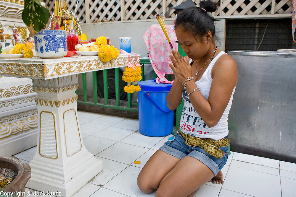 01 MARCH 2008 -- BANGKOK, THAILAND: A woman prays at a Buddhist shrine on Soi Nana, in one of adult entertainment districts in Bangkok, Thailand.     Photo by Jack Kurtz