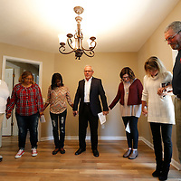 Thomas Wells | Northeast Mississippi Daily Journal<br /> Rev. Tommy Galloway, center, bless the house of Tamara Norman, center, left, to finish the dedication for her Habitat for Humanity home on Monday.