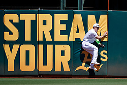 OAKLAND, CA - AUGUST 25:  Mark Canha #20 of the Oakland Athletics catches a fly ball hit off the bat of Evan Longoria (not pictured) of the San Francisco Giants during the first inning at the RingCentral Coliseum on August 25, 2019 in Oakland, California. The San Francisco Giants defeated the Oakland Athletics 5-4. Teams are wearing special color schemed uniforms with players choosing nicknames to display for Players' Weekend. (Photo by Jason O. Watson/Getty Images) *** Local Caption *** Mark Canha