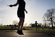 The day after UK Prime Minister Boris Johnson imposed unprecedented restrictions of movement for millions of Britons who were told to stay at home unless their key jobs or journeys were essential. Told to take a single exercise session per day, self-employed Russell who has been displaced from the indoor gym at Brockwell Lido, jumps with his skipping rope at a clear space for those wishing to work out on a soft surface, where south Londoners use their local green space for a daily activity in Brockwell Park in Herne Hill SE24, on 24th March 2020.