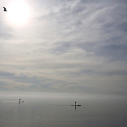 A tranquil scene in Madison, Connecticut as two paddle boarders enjoy Christmas day as they paddle on calm waters while a heat mist rises from the sea. Temperatures again reached over 60 degrees setting more records for high temperatures in December. Madison, Connecticut, USA. 25th December 2015. Photo Tim Clayton