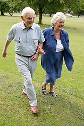 Older couple walking briskly in the park,