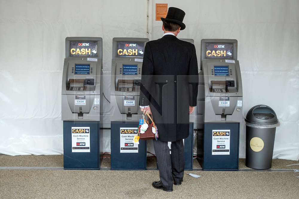 © Licensed to London News Pictures. 18/06/2014. Ascot, UK. A man waits for money from an ATM. Day two at Royal Ascot 18th June 2014. Royal Ascot has established itself as a national institution and the centrepiece of the British social calendar as well as being a stage for the best racehorses in the world. Photo credit : Stephen Simpson/LNP
