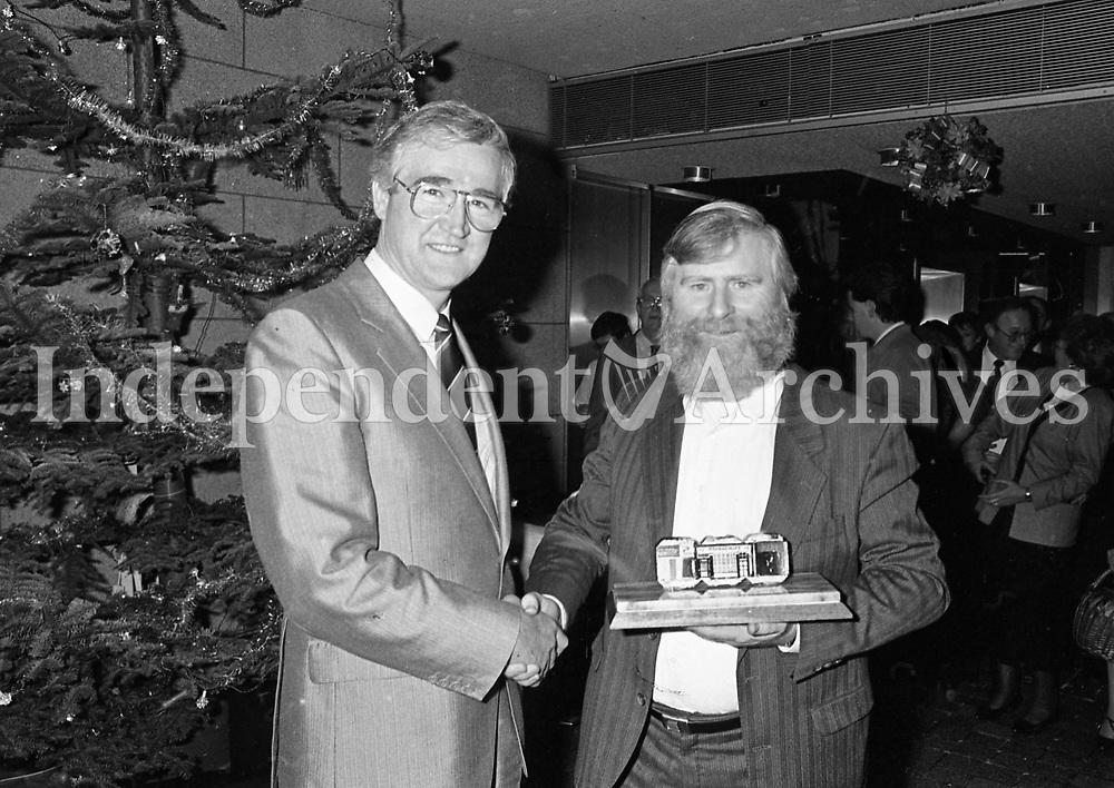 """John Sheahan, Composer and member of The Dubliners who Composed the song """"The Marino Waltz"""", being presented with a Peat Briquette with a picture of O'Donoghues Pub on it by Eddie O'Connor, Managing Director of Bord na Mona in the offices in Baggot Street in Dublin, 17/12/1987 (Part of the Independent Newspapers Ireland/NLI Collection)."""