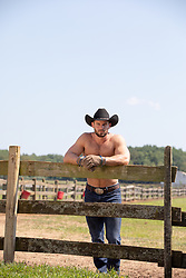 shirtless muscular cowboy hanging out on a wooden fence