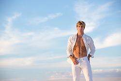 sexy blond man with open shirt outdoors