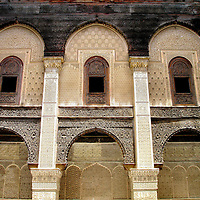 Madrasa al-Attarine Courtyard in Fes el Bali at Fez, Morocco <br /> Located off a decrepit alley near a spice souk is this beautiful madrasa. The school for the Koranic religion was commissioned by a sultan from the Banū Marīn dynasty. His name was Abū Sa&rsquo;īd Uthmān II and he reigned over Morocco from 1310 to 1331.  In the courtyard is a masterpiece of architecture, with its mosaic ornate tiles, carved cedar wood and marble columns.  In front of these arches (not in picture) is a checkerboard tile floor and fountain.