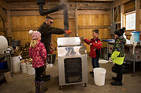 Michael Bolduc explains how the maple syrup evaporator will boil sap to make maple syrup to 2nd graders Alison Nutter, Brent Howard and Jacoby Drouin in their new Sap House at Gilford Elementary School.  (Karen Bobotas/for the Laconia Daily Sun)