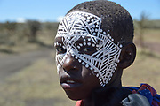 A teenage Maasai with painted face after the 'emorata' ceremony, which is the circumcision and right of passage to become a member of the warrior or 'moran' class. Maasai is an ethnic group of semi-nomadic people Photographed in Tanzania
