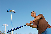 Senior man swinging baseball bat
