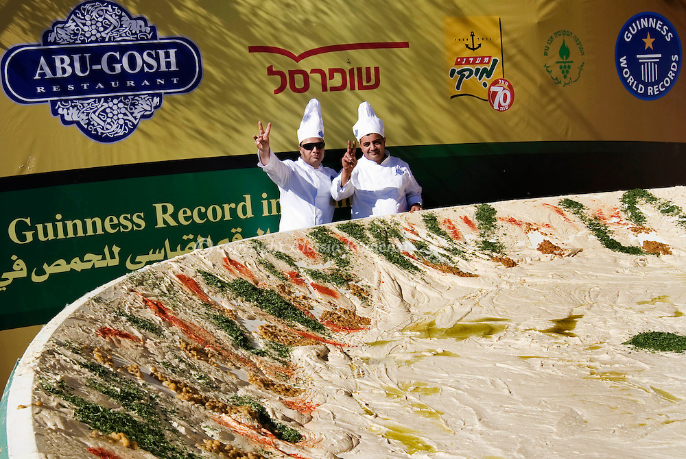 Chefs pose next to a giant serving of hummus resting on a six-meters (20 foot) satellite dish during an attempt to break a new world record in the Arab Israeli village of Abu Gosh on January 8, 2010. Fifty chefs in the Arab-Israeli village of Abu Ghosh mashed up over four tonnes of hummus, beating the Guinness World Record set in Lebanon just months ago. This is a new record,' said Guinness adjudicator Jack Brookbank as the massive dip, dished out in a six-metre (20 foot) satellite dish provided by sponsors, weighed in at 4,087.5 kilos (8992.5 pounds). That is about twice as much as the previous record set in October in neighbouring Lebanon, Israel's political and culinary rival..© ALESSIO ROMENZI