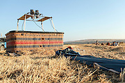 Hot air balloon basket on the ground photographed in the Jezreel Valley, Israel Mount Gilboa in the background
