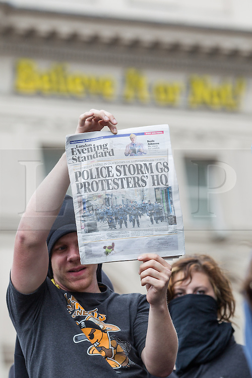 """© Licensed to London News Pictures . 11/06/2013 . London , UK . """" Stop G8 """" anti capitalist protesters in  Piccadilly Circus , London today (Tuesday 11th June 2013) holding a copy of the London Evening Standard with the headline """" Police Storm G8 Protesters HQ"""" . This  ahead of Britain hosting the 39th G8 summit on 17th/18th June at the Lough Erne Resort , County Fermanagh , Northern Ireland , next week . Photo credit : Joel Goodman/LNP"""