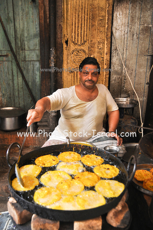 man frying food in his food stall Jodhpur, Rajasthan, India