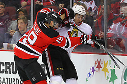 Dec 18, 2013; Newark, NJ, USA;  New Jersey Devils center Travis Zajac (19) hits Ottawa Senators center Mika Zibanejad (93) during the first period at the Prudential Center.