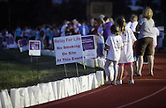 Goshen, New York - People stand around the track, which is lined with luminaria in remembrance of cancer victims, during the Relay for Life at Goshen High School on June 19, 2011. The Relay for Life is the American Cancer Society's signature fundraising event. Participants celebrate the lives of people who have battled cancer, remember loved ones lost, and fight back against the disease by raising money.