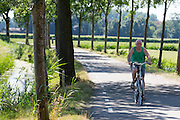 In Zeist rijdt een oudere man op de fiets in de hitte langs de weilanden.<br /> <br /> In Zeist a man cycles in the heat near the pastures.