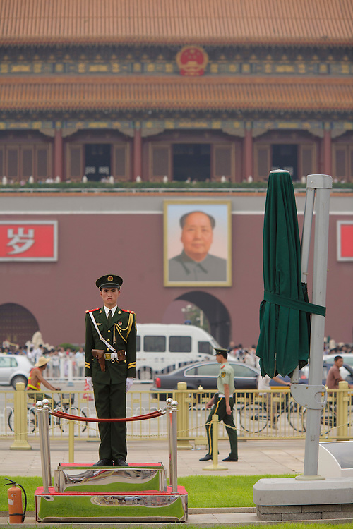 Soldier at Tian'anmen Square with the portrait of Mao Zedong hang on the Forbidden City's facade